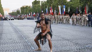Un des huit guerriers maoris présents lors du défilé militaire du 14 juillet 2016 s'adonnent à des gestes traditionnels. (THOMAS SAMSON / AFP)