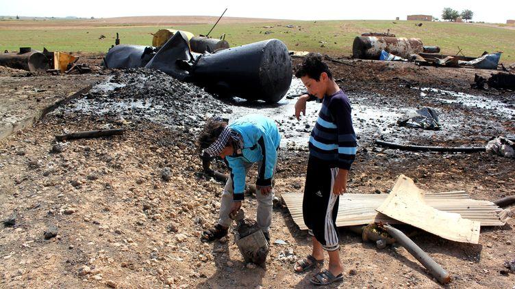 Des enfants jouent dans les décombres d'une raffinerie bombardée par l'armée américaine, dans les environs de Tal Abyad (Syrie), le 2 octobre 2014. (AFP)