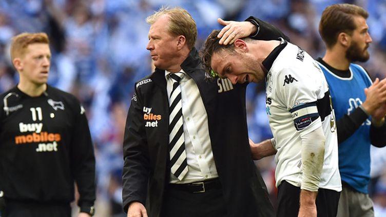 Steve McClaren, réconfortant ses joueurs à l'issue du barrage contre QPR. (BEN STANSALL / AFP)