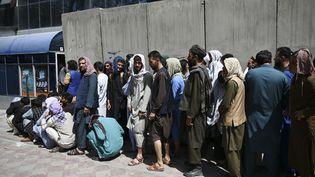 Des Afghans font la queue à l'entrée d'une banque pour retirer de l'argent, dans le quartier deShar-e-Naw à Kaboul, le 4 septembre 2021. (WAKIL KOHSAR / AFP)