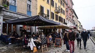 Des clients sont assis à la terrasse de bars et de restaurants, le 6 février 2021, à Milan (Italie). (MIGUEL MEDINA / AFP)