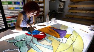 Maya Husseini, maître-verrier, travaille sur un vitrail pour une cathédrale, en septembre 2020. (ANWAR AMRO / AFP)