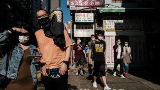 Des piétons portant des masques, à Hong Kong, le 16 avril 2020. (ANTHONY WALLACE / AFP)