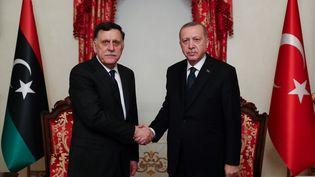 Poignée de mains entre le chef du gouvernement libyen Fayez al-Sarraj (à gauche) et le président turc Recep Tayyip Erdogan lors d'une réunion à Istanbul le 20 février 2020. (MURAT CETINMUHURDAR / TURKISH PRESIDENTIAL PRESS SERVI)