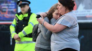 Une mère et sa fille aux abords de laManchester Arena (Angleterre), au lendemain de l'attentat, le 23 mai 2017. (LINDSEY PARNABY / ANADOLU AGENCY)