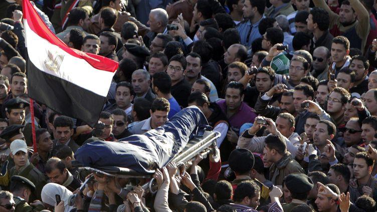 La foule porte la dépouille d'un des 14 policiers tués dans l'attentat à la voiture piégé de Mansoura (Egypte), le 24 décembre 2013. (MOHAMED ABD EL GHANY / REUTERS)