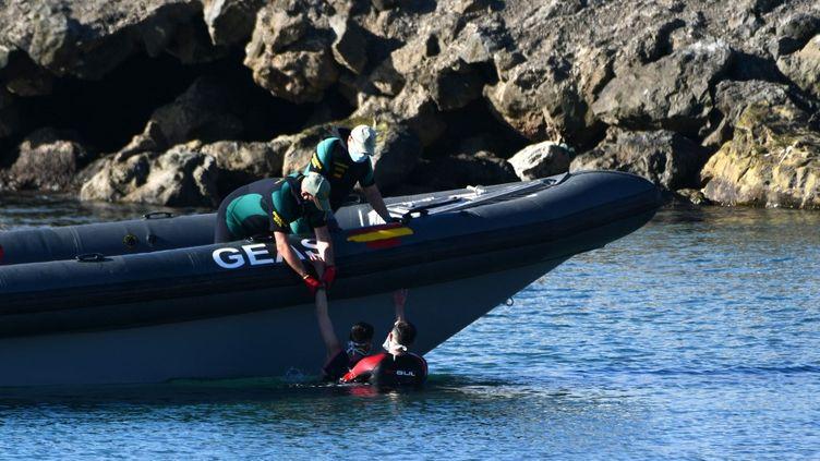 Les gardes civils espagnolsau secours d'un migrant, après son arrivée à la nage dans l'enclave espagnole de Ceuta en provenance du Maroc voisin, le 17 mai 2021. (ANTONIO SEMPERE / AFP)