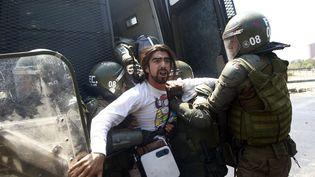 La police chilienne arrête un homme à Santiago, le 20 octobre 2019. (PABLO VERA / AFP)
