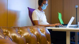 Un homme porte un masque pour travailler dans un espace de coworking (ou cotravail), à Toulouse, le 25 août. (PATRICIA HUCHOT-BOISSIER / HANS LUCAS)