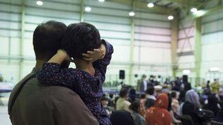 """Des personnes ayant fui l'Afghanistan attendant un autre vol sur la base aérienne d'Al Dhafra, près d'Abu Dhabi, dans le cadre de l'opération """"Apagan"""", le 21 août 2021. (PHILIPPINE GAUTIER / ETAT MAJOR DES ARMEES / AFP)"""