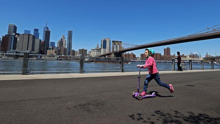 Une enfant sur une trottinette, à New York (Etats-Unis), le 28 avril 2020. (AL BELLO / GETTY IMAGES NORTH AMERICA / AFP)
