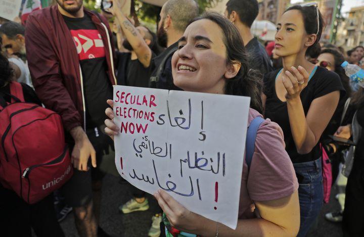 """Une manifestante libanaise brandit une pancarte sur laquelle est inscrit""""abolir le système sectaire corrompu"""", le 31 octobre 2019, à Beyrouth. (JOSEPH EID / AFP)"""