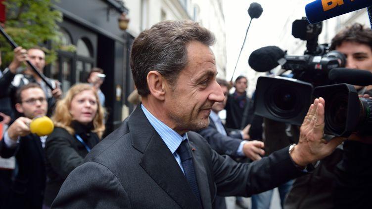 L'ancien président Nicolas Sarkozy est assailli par les journalistes au sortir d'un déjeuner avec François Fillon, le 24 octobre 2012 à Paris. (ERIC FEFERBERG / AFP)