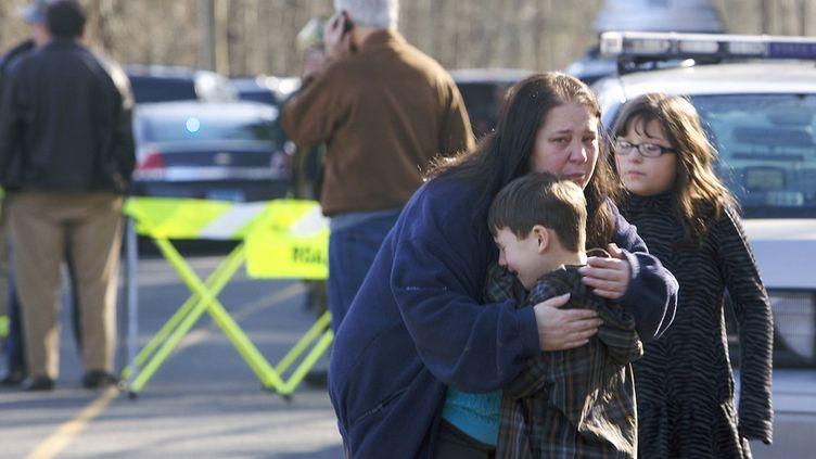 Une femme réconforte un petit garçon devant l'école primaire de Newtown (Connecticut) où une fusillade a éclaté, le 14 décembre 2012. (MICHELLE MC LOUGHLIN / REUTERS )