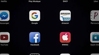 Des applications Google, Amazon, Facebook et Apple (Gafa) sur une tablette, en avril 2018. (LIONEL BONAVENTURE / AFP)