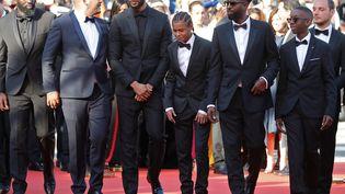 Le réalisateur Ladj Ly (au centre, avec les lunettes) entouré de son équipe. Pour sa première venue à Cannes, il est sélectionné dans la compétition officielle pour Les Misérables. (VALERY HACHE / AFP)