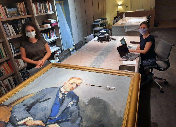 La directrice et une restauratrice du musée Sursock, dans le quartier d'Achrafieh, devant un portrait de Nicolas Sursock, déchiré par l'explosion qui a frappé Beyrouth le 4 août 2020. (AURÉLIEN COLLY / ESP - REDA INTERNATIONALE)
