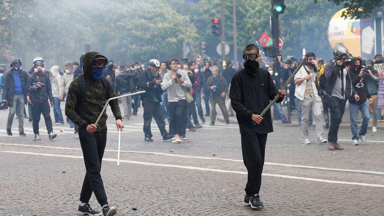 Des manifestants armés de bâtons font face aux forces de l'ordre, le 17 mai 2016 place Denfert-Rochereau à Paris, lors d'une manifestation contre la loi Travail. (THOMAS SAMSON / AFP)