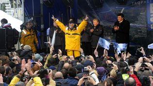 Loïck Peyron célèbre son retour sur terre après avoir remporté le Trophée Jules-Verne avec son équipage, le 7 janvier 2012 à Brest (Finistère). (DAMIEN MEYER / AFP)