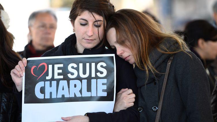 Des personnes tiennent une pancarte après avoir observé une minute de silence sur le vieux port à Marseille (Bouches-du-Rhône). (ANNE-CHRISTINE POUJOULAT / AFP)