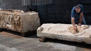 Les services d'archéologie israéliens nettoient un riche sarcophage romain exhumé, le 3 septembre 2015 à Bet Shemesh.  (Menahem Kahana / AFP)
