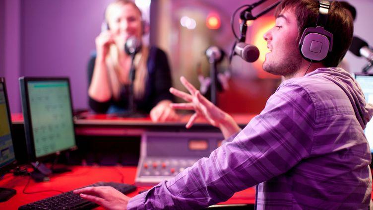 Un homme et une femme dans un studio radio. (ZERO CREATIVES / CULTURA CREATIVE / AFP)