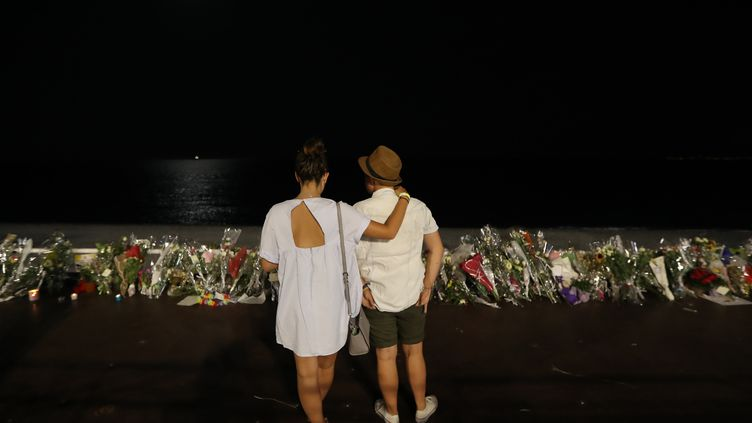 Deux personnes regardent les hommages déposés pour les victimes de l'attentat de Nice (Alpes-Maritimes), le 18 juillet 2016, sur la promenade des Anglais. (VALERY HACHE / AFP)