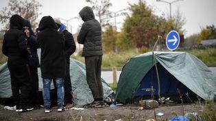 Des migrants échangent à côté de leur tente dans un camp de Calais (Pas-de-Calais), le 15 novembre 2019 (illustration). (FRANCOIS LO PRESTI / AFP)