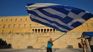 Un homme agite le drapeau grec devant la place du parlement grec à Athènes. (CITIZENSIDE/NICOLAS KOUTSOKOSTAS / CITIZENSIDE.COM)
