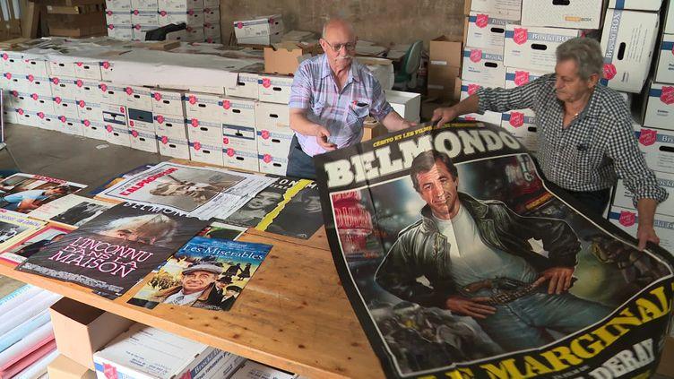 Claude Bertin-Denis (à gauche sur l'image) en pleine préparation de l'exposition-hommage à Jean-Paul Belmondo. (France 3 Franche-Comté)