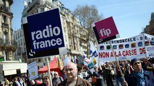 Des manifestants brandissant des pancartes de soutien à la grève des salariés de Radio France lors d'un rassemblement contre l'austérité, jeudi 9 avril à Paris. (STEPHANE DE SAKUTIN / AFP)