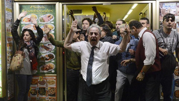 """Des manifestants se réfugient dans un restaurant alors que des heurts éclatent entre des """"indignés"""" et les forces de l'ordre, à Madrid (Espagne), le 25 septembre 2012. (PIERRE-PHILIPPE MARCOU / AFP)"""