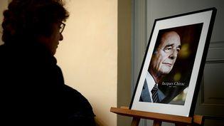 Une femme se recueille devant un portrait de l'ancien président, Jacques Chirac, le 29 septembre 2019. (PHILIPPE LOPEZ / AFP)