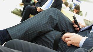 Un homme en costume consulte son amartphone assis dans un aéroport. (MAXPPP)