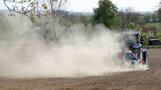 Un tracteur soulève un nuage de poussière à son passage dans un champ à proximité du village de Hunspach dans le Bas-Rhin, le 13 avril 2017. (JEAN-MARC LOOS / MAXPPP)