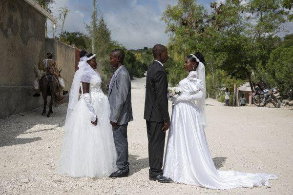 Patricia, enceinte, et Obelson se sont mariés au cours d'une cérémonie collective. Ils posent devant l'église avec un autre couple qu'ils ne connaissent pas. Conducteur de motocyclette, Obelson a rencontré Patricia pendant qu'il travaillait. Patricia enceinte, ses parents ont exigé qu'Obelson l'épouse. Les protestants en Haïti préconisent le mariage, surtout si le couple attend un enfant. Dans certaines écoles religieuses, les parents doivent présenter leur certificat de mariage pour inscrire leurs enfants. Baie-de-Henne, Haïti, 27 octobre 2018.  (© Valérie Baeriswyl / Reuters)
