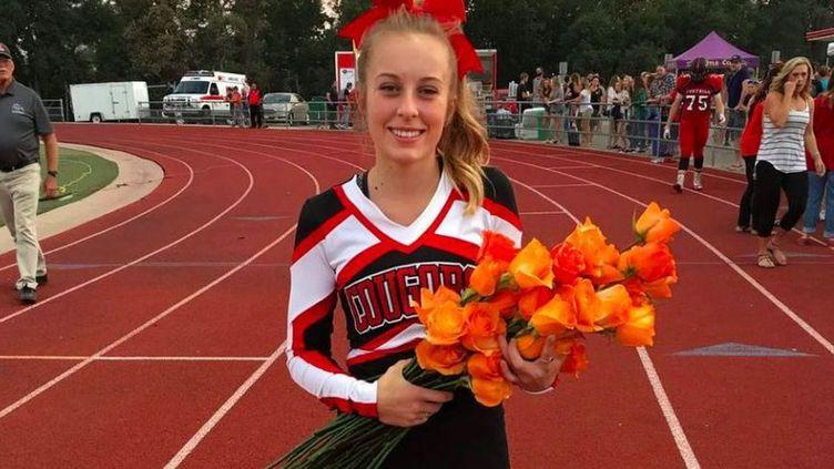 Ashley Adamietz pose, émue, avec les fleurs qu'elle a reçues des joueurs de l'équipe de football de son lycée, à Palo Cedro (Californie). (WATCH SPORTS 1 / YOUTUBE)