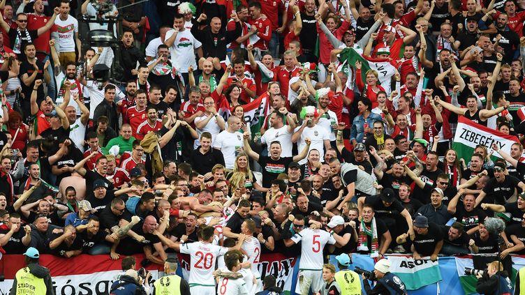 Les joueurs hongrois fêtent leur victoire face à l'Autriche avec leurs supporters. (NICOLAS TUCAT / AFP)