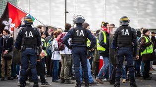 """Des forces de l'ordre devant des manifestants, lors du 56e samedi de mobilisation des """"gilets jaunes"""", le 7 décembre 2019 à Paris. (AMAURY CORNU / HANS LUCAS / AFP)"""