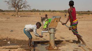 Des enfants près d'un puits dans un village au Burkina Faso (Antoine BOUREAU / AFP)