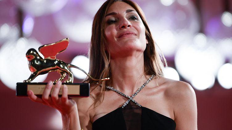 """La réalisatrice Audrey Diwan pose avec le Lion d'or du meilleur film qu'elle a reçu pour """"L'Événement"""" après la cérémonie de clôture du 78e Festival du film de Venise, le 11 septembre 2021 au Lido de Venise. (FILIPPO MONTEFORTE / AFP)"""