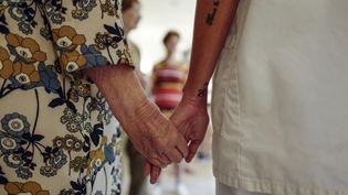 """Une enseignante d'art-thérapie tient la main d'une résidente de la """"Maison Saint-Jean Hélios"""", un Ehpad situé à Nice (Alpes-Maritimes), le 4 août 2020. (VALERY HACHE / AFP)"""