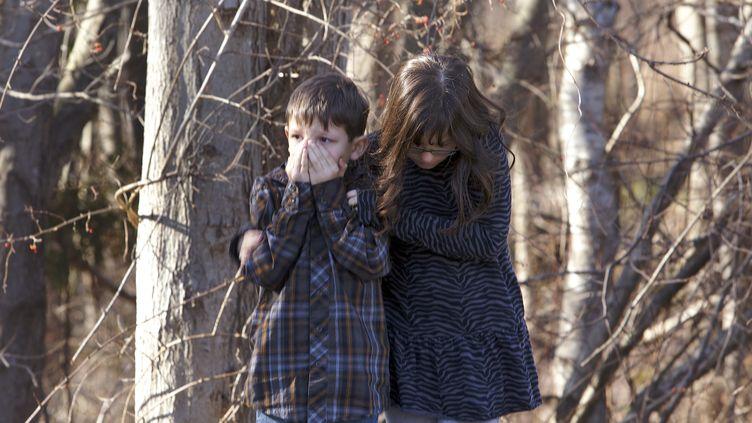 Deux enfants attendent à l'extérieur de l'école primaire Sandy Hook (Connecticut, Etats-Unis), après la fusillade qui a fait au moins 27 morts, le 14 décembre 2012. (MICHELLE MCLOUGHLIN / REUTERS)