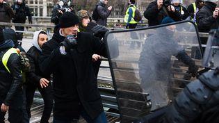 """Face-à-face entre des gendarmes et des manifestants lors d'un rassemblement de """"gilets jaunes"""" à Paris, le 5 janvier 2019. (MARION VACCA / HANS LUCAS / AFP)"""