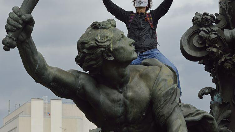 Un manifestant juché sur la statue de la place de la République, le 10 septembre 2013 à Paris, lors d'un défilé contre la réforme des retraites. (ERIC FEFERBERG / AFP)