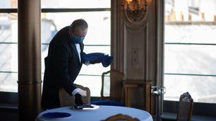 Un serveur dresse une table au restaurant La Tour d'Argent, à Paris, le 2 septembre 2020. (MARTIN BUREAU / AFP)