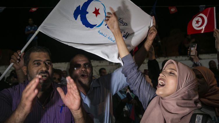 Partisans de la formation d'inspiration islamiste Ennahdha à Tunis le 6 octobre 2019 sur arrière-fond de drapeau nahdaoui (à gauche) et tunisien (à droite). (RIADH DRIDI/AP/SIPA / SIPA)