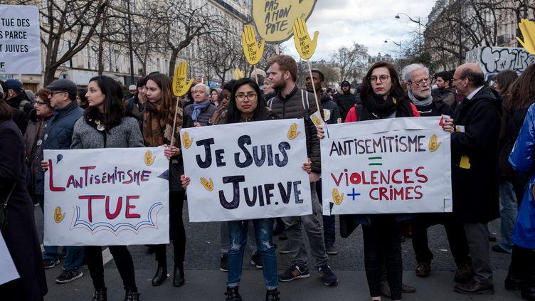 Des manifestants portent des pancartes dénonçant l'antisémitisme, le 28 mars 2018, à Paris, pendant une marche blanche en hommage à Mireille Knoll, octogénaire juive tuée dans la capitale. (BENJAMIN FILARSKI / HANS LUCAS / AFP)
