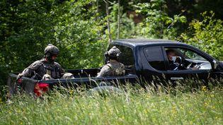 Des membres du GIGN sont assis à l'arrière d'un pick-up lors de la recherche d'un homme qui a abattu deux personnes dans une scierie près du village de Plantiers dans les Cévennes, le 12 mai 2021. (CLEMENT MAHOUDEAU / AFP)