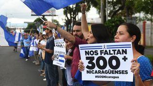 """Des manifestants anti-gouvernement tiennent des pancartes """"300 Nicaraguayens manquent"""", alors qu'ils forment une chaîne humaine à Managua, capitale du Nicaragua, le 4 juillet 2018. (MARVIN RECINOS / AFP)"""